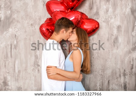 Young couple with heart shaped red balloons kissing near grey wall #1183327966