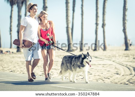 Young couple with husky dog in Santa monica. Concept with people and animals