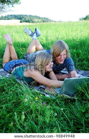 young couple with laptop outdoors in summer