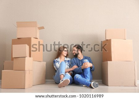 Young couple with moving boxes on floor in room