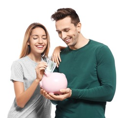 Young couple with piggy bank on white background