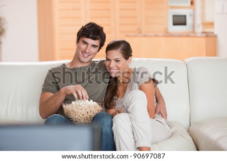 Young couple with popcorn on the sofa watching a movie