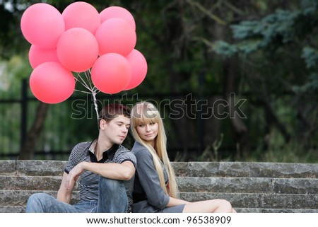 young couple with red balloons on natural background - stock photo