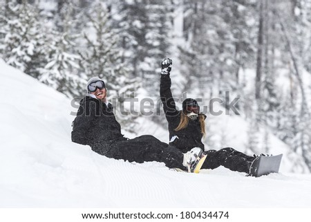 young couple with snowboards sitting on fresh snow in the mountains of northern Idaho