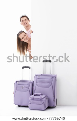 Young couple with suitcases and empty billboard on a white background