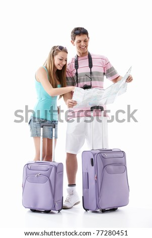 Young couple with suitcases see map on a white background