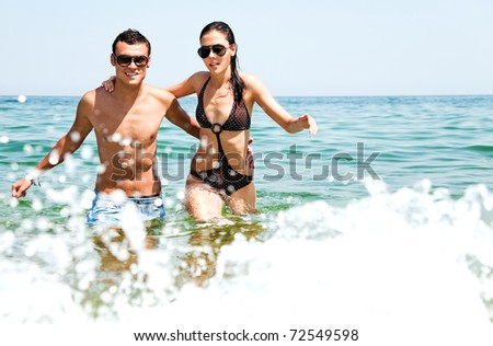 Young couple with sunglasses hugging and going out of sea - stock photo