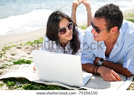 Young couple with sunglasses lying on beach behind laptop, looking each other