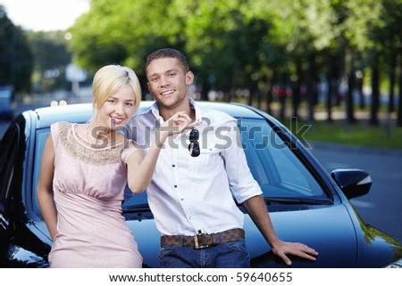 Young couple with the keys in car - stock photo