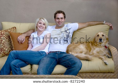 young couple with their dog sitting on couch - stock photo