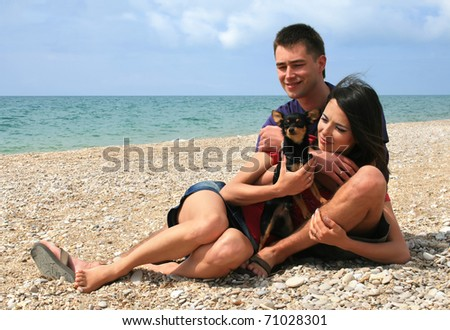 Young couple with their pet having a good time on a beach