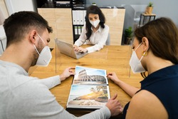 Young Couple With Travel Agent Wearing Face Mask