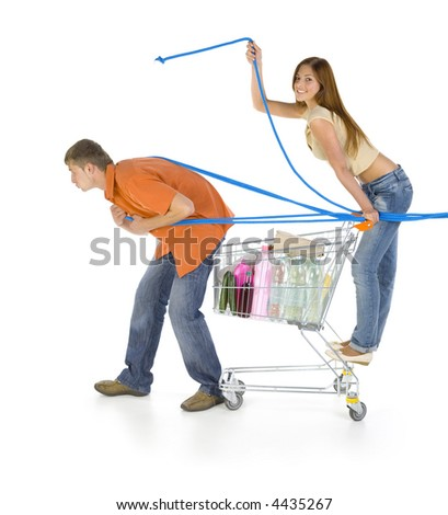 Young couple with trolley. Boy is pulling full troley with girl. Girl is looking at camera and smiling. White background, side view. Whole body - stock photo