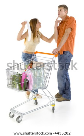 Young couple with trolley. Discussing about shop bill. Boy thinking about something and smiling, girl is angry. Isolated on white in studio, whole body