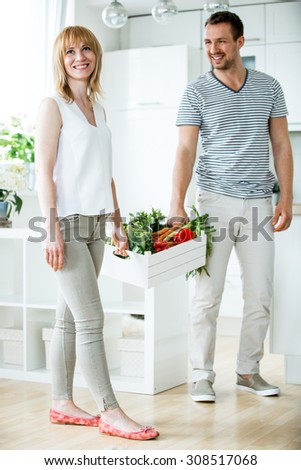 Young couple with vegetable box in kitchen