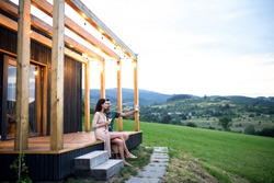 Young couple with wine outdoors, weekend away in container house in countryside.