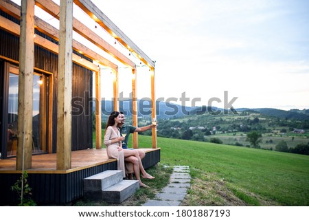 Photo of  Young couple with wine outdoors, weekend away in container house in countryside.