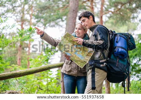 Young couple, woman and man, on hike looking for the right trail on map