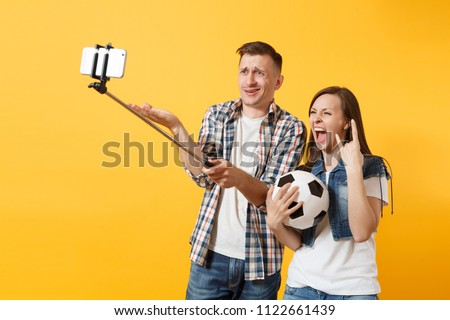Young couple woman man, football fans doing selfie on mobile phone with monopod selfish stick, cheer up support team, soccer ball isolated on yellow background. Sport family leisure lifestyle concept