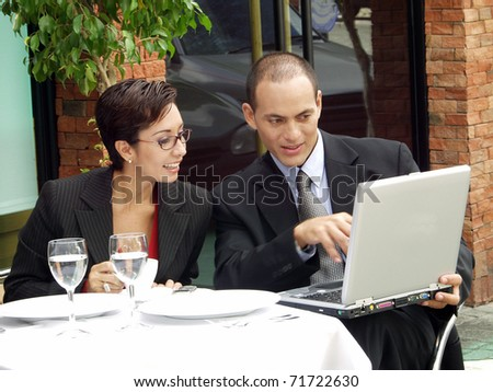 Young couple working in a cafe using a laptop.
