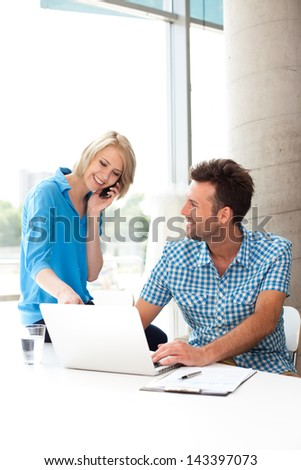 Young couple working together on a laptop in the office. Teamwork concepts.