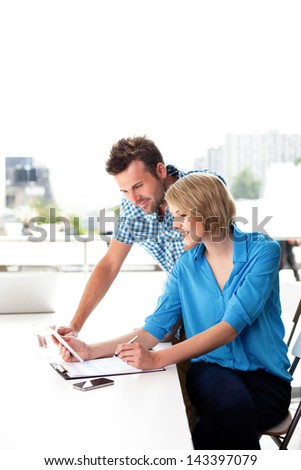 Young couple working together on digital tablet in the office. Teamwork concepts.