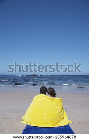 Young couple wrapped in a towel on beach