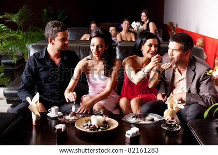young couples eating deserts feeding each other