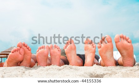 Young couples feet at the  sandy beach