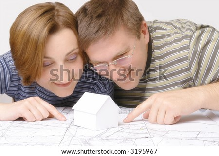 Young couples looking closely at building plan with white little cardboard house model
