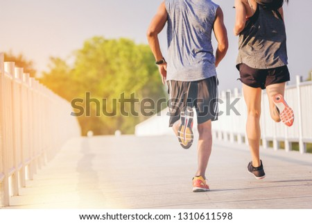 Young couples running sprinting on road. Fit runner fitness runner during outdoor workout #1310611598