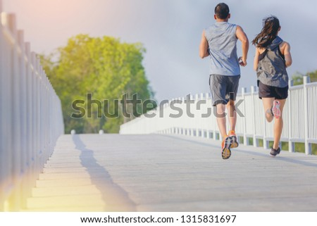 Young couples running sprinting on road. Fit runner fitness runner during outdoor workout #1315831697