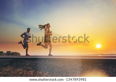 Young couples running sprinting on road. Fit runner fitness runner during outdoor workout with sunset background #1347893981