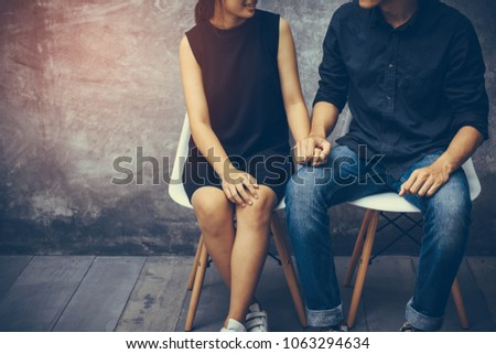 Young couples sitting on a chair inside the room which walls are made from cement. They shake hands, show their love and encouragement toward each other with copy space.