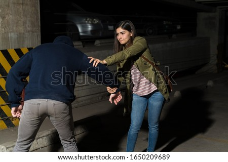 Young courageous woman defending herself from attacking criminal in alley Stock photo ©