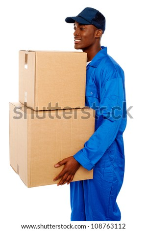 Young courier boy moving boxes looking away. Great services