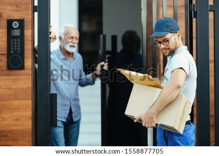 Young courier delivering packages to customer's home.  #1558877705