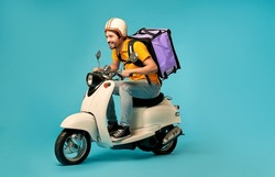 Young courier, delivery man in uniform with thermo backpack on a moped isolated on blue background. Fast transport express home delivery. Online order.