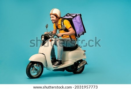 Young courier, delivery man in uniform with thermo backpack on a moped isolated on blue background. Fast transport express home delivery. Online order. Stockfoto ©