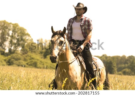 young cowboy man ridig with horse