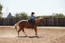 Young cowboy riding palomino horse through outdoor arena for western lifestyle on ranch.