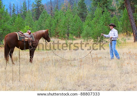 Young cowboy training his horse in the meadows