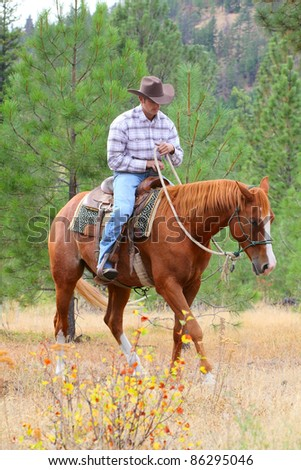Young cowboy training his horses in a meadow