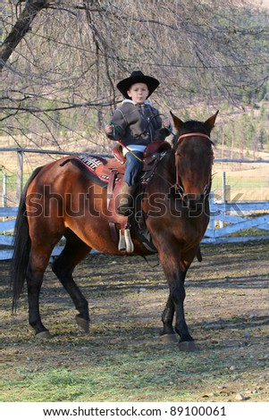 Young cowboy with hat riding his horse