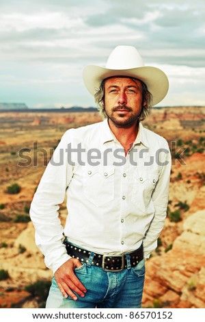 Young cowboy with white hat and shirt standing in desert landscape with cloudy sky, USA.