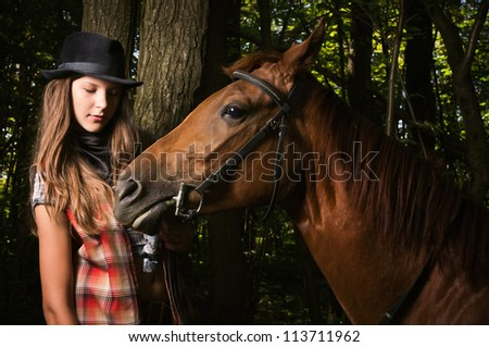 Young cowgirl in hat with bay horse