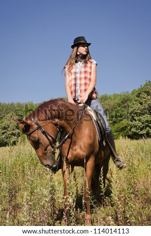 Young cowgirl riding a bay horse