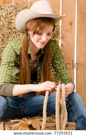 Young cowgirl western country style sitting in barn