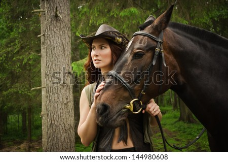 Young cowgirl with brown horse in the forest