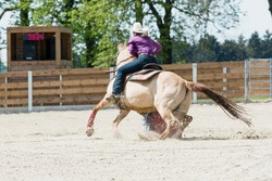 Young cowgirl with hat riding a beautiful paint horse in a barrel racing event at a rodeo in Mitrov, Czech republic